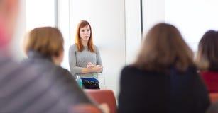 Kvinna som ger presentation i hörsal på universitetet arkivfoto