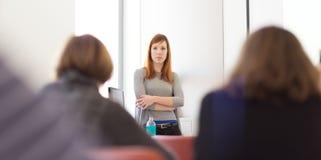 Kvinna som ger presentation i hörsal på universitetet arkivbild