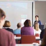 Kvinna som ger presentation i hörsal på universitetet arkivbilder