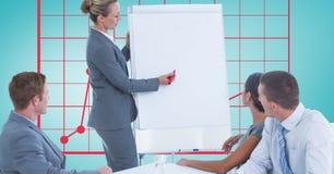 Kvinna som ger presentation till kollegor mot graf royaltyfri bild