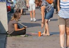 Kvinna som ger sig till panhandleren Royaltyfri Fotografi