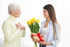 Kvinna som ger tulpan och g?vaasken till hennes mogna moder arkivfoton