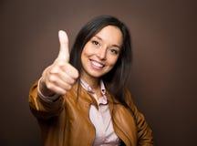Kvinna som ger tummar upp att le för gest för godkännandehandtecken Arkivfoton