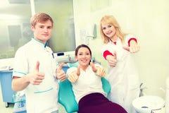 Kvinna som ger upp tummar på tandläkarekontoret Arkivbild
