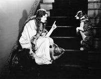 Kvinna som grälar på hunden på trappa (alla visade personer inte är längre uppehälle, och inget gods finns Leverantörgarantier at Royaltyfria Bilder