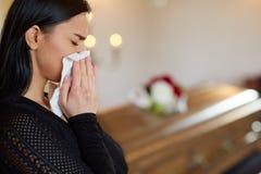 Kvinna som gråter nära kistan på begravningen i kyrka arkivbilder