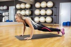 Kvinna som gör liggande armhävningar på Mat In Gym Fotografering för Bildbyråer
