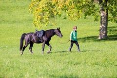 Kvinna som går med hästen Royaltyfria Bilder