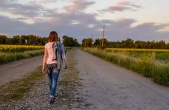 Kvinna som går ner en landsväg Arkivfoto