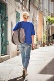 Kvinna som går på den gamla lappade gatan Royaltyfria Bilder