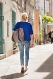 Kvinna som går på den gamla lappade gatan Royaltyfri Foto