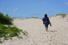 Kvinna som går på sanden Arkivfoto