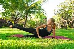 Kvinna som gör yoga i trädgård Arkivfoton