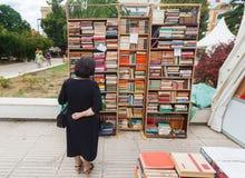 Kvinna som granskar bokhyllor på gatamarknad Fotografering för Bildbyråer