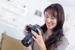 Kvinna som granskar foto p? sk?rmen f?r digital kamera royaltyfria foton