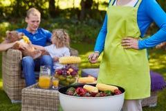 Kvinna som grillar mat Arkivfoto