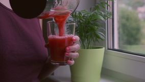 Kvinna som häller den röda coctailen in i exponeringsglaset, ultrarapidvideo arkivfilmer