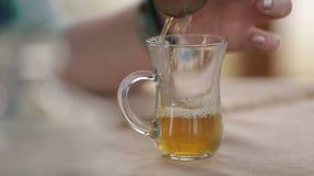 Kvinna som häller försiktigt bärnstensfärgat te in i exponeringsglas, friskhet och kvalitet av drinken stock video