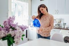 Kvinna som häller filtrerat vatten från filtertillbringaren in i exponeringsglas på kök modernt designkök Sund livsstil royaltyfri foto
