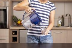 Kvinna som häller filtrerat vatten in i ett exponeringsglas royaltyfria foton