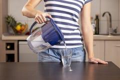 Kvinna som häller filtrerat vatten in i ett exponeringsglas arkivfoton