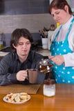 Kvinna som häller varmt te i ung mans kopp Royaltyfri Bild