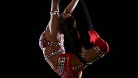 Kvinna som hänger i cirkeln för flyg- akrobatik Svart bakgrund långsam rörelse close upp lager videofilmer