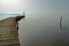 Kvinna som håller ögonen på över Trasimeno laken, Italien Arkivfoton