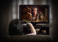 Kvinna som håller ögonen på den esoteriska TV-kanal på en soffa Arkivfoto