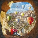 Kvinna som håller ögonen på som färgrika ballonger för varm luft som flyger över dalen på Cappadocia Arkivbild
