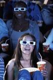 Kvinna som håller ögonen på filmen 3D i teater Fotografering för Bildbyråer