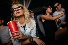 Kvinna som håller ögonen på filmen 3D i teater Arkivfoto
