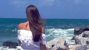 Kvinna som håller ögonen på havet med vågor som kraschar ultrarapid