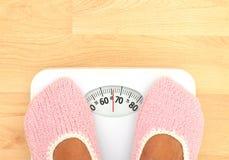 Kvinna som håller ögonen på henne att weight - detaljen, på scales Arkivbild