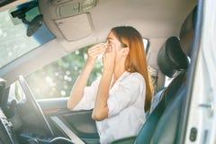 Kvinna som håller ögonen på hennes makeup i spegeln, medan köra en bil och ett försök för att kyla sig på den varma soliga dagen Royaltyfria Foton