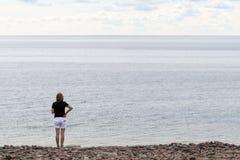 Kvinna som håller ögonen på horisonten Arkivfoto