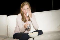 Kvinna som håller ögonen på ledsen film på TV Royaltyfria Bilder