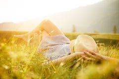 Kvinna som håller ögonen på solnedgången Serenitet och avkoppling royaltyfria bilder