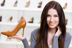 Kvinna som håller den bruna skon royaltyfri foto