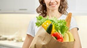 Kvinna som håller den pappers- påsen med mat på kök arkivfoto