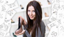 Kvinna som håller denfärgade skon white för shopping för försäljning för bakgrundsjulflicka lycklig arkivfoto