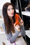 Kvinna som håller en sko på shoppa fotografering för bildbyråer