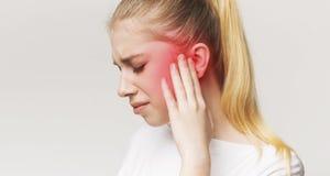 Kvinna som har örat att smärta och att trycka på hennes smärtsamma huvud royaltyfri bild