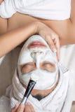 Kvinna som har den ansikts- maskeringen på skönhetsalongen Arkivfoton