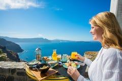 Kvinna som har den läckra frukosten i lyxig semesterort i medelhavs- Arkivbilder
