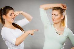 Kvinna som har den våta armhålan hennes vän som luktar stank Royaltyfri Foto