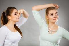 Kvinna som har den våta armhålan hennes vän som luktar stank Royaltyfria Foton