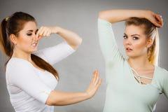 Kvinna som har den våta armhålan hennes vän som luktar stank Fotografering för Bildbyråer