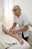 Kvinna som har en benmassage Arkivbild
