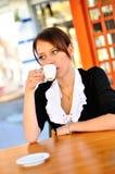 Kvinna som har en kopp av kaffe på lunchen Arkivbilder